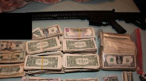 A rifle and cash seized during a police raid targeting a street gang in Long Beach on Feb. 14, 2020. (Credit: Long Beach Police Department)