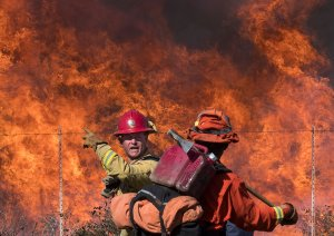 A firefighter speaks to an inmate firefighter as they prepare to put out flames on the road leading to the Reagan Library during the Easy Fire in Simi Valley on Oct. 30, 2019.(Credit: Mark Ralston/AFP via Getty Images)