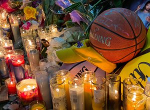 Candles are displayed at a makeshift memorial in front of a mural for former NBA and Los Angeles Lakers player Kobe Bryant in downtown Los Angeles on January 26, 2020 as people pay tribute to the former basketball player following his death in a helicopter crash near Los Angeles. (Credit: CHRIS DELMAS/AFP via Getty Images)