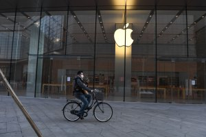 A man cycles past a closed Apple store in Beijing on Feb. 8, 2020. (Credit: GREG BAKER/AFP via Getty Images)