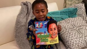 "Soloman, 7, is seen holding the children's book he wrote, entitled, ""Soloman's Socks."" (Credit: KTLA)"