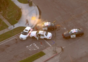 Officers surround a sedan in Long Beach following a pursuit in the South Bay on Feb. 11, 2020. (Credit: Sky5)